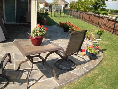 The flagstone patio in this fairly small backyard is well integrated with the curving shape of the flag stone patio and the curving lawn work well together.